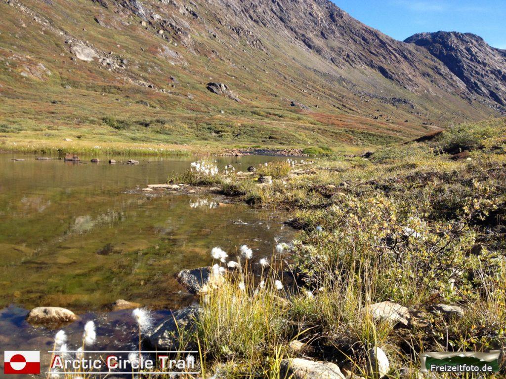Kurze Pause am Fluss. Hier wächst Wollgras.