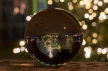 Glaskugel vor einem Weihnachtsbaum